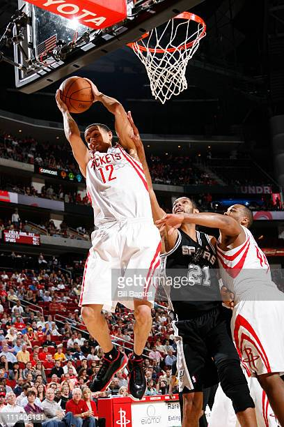 Kevin Martin of the Houston Rockets rebounds the ball over Tim Duncan of the San Antonio Spurs on April 1 2011 at the Toyota Center in Houston Texas...
