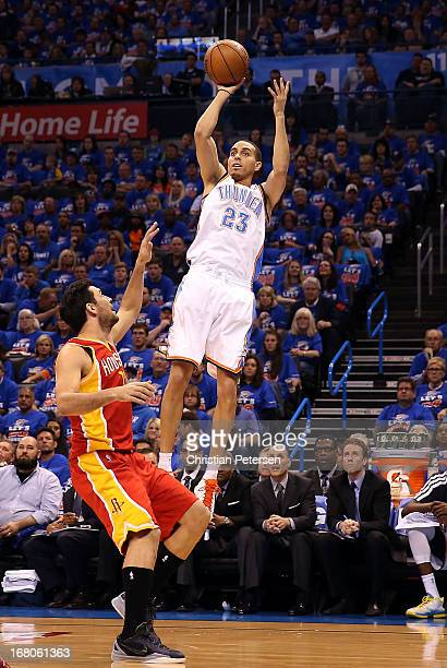 Kevin Martin of the Oklahoma City Thunder puts up a shot over Carlos Delfino of the Houston Rockets during Game Five of the Western Conference...