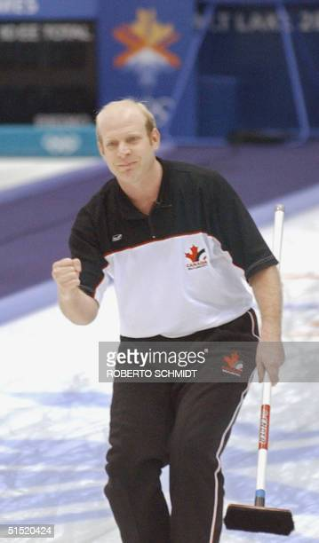 Kevin Martin the skip for the Canada men's curling team pumps his fist after he delivered the last rock to score and beat the Swedish team 20...