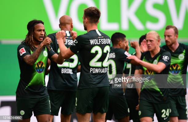 Kevin Mbabu of VfL Wolfsburg celebrates with teammates after scoring his team's first goal during the Bundesliga match between VfL Wolfsburg and...