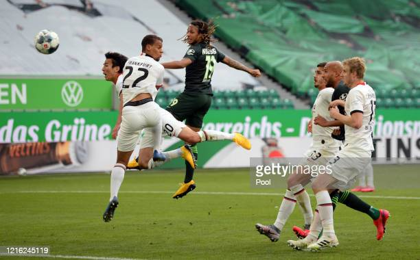 Kevin Mbabu of VfL Wolfsburg scores his team's first goal past Makoto Hasebe and Timmy Chandler of Eintracht Frankfurt during the Bundesliga match...