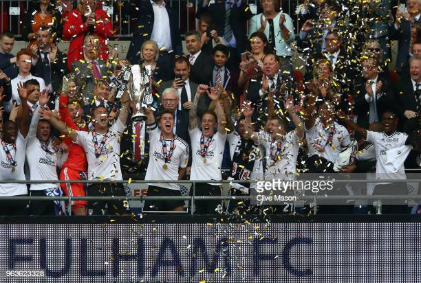 Kevin McDonald of Fulham and Tom Cairney of Fulham lift the trophy following their sides victory in the Sky Bet Championship Play Off Final between...