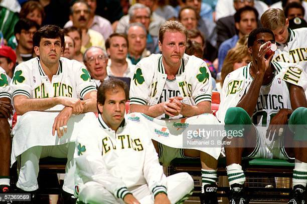 Kevin McHale Larry Bird and Robert Parish of the Boston Celtics look on from the bench during a game played in 1991 at the Boston Garden in Boston...