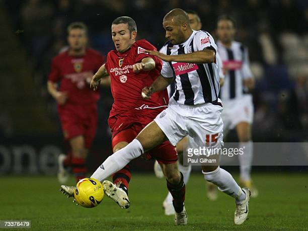 Kevin McNaughton of Cardiff City battles for the ball with Dimonansy Kamara of West Bromwich Albion during the CocaCola Championship match between...