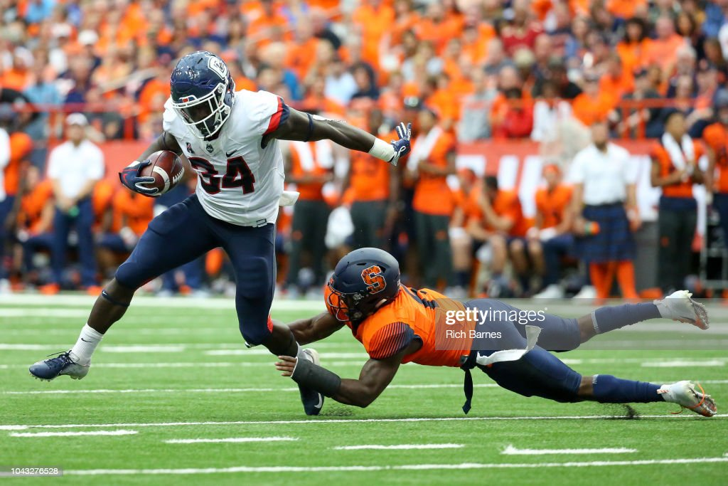 Kevin Mensah of the Connecticut Huskies runs with the ball ...