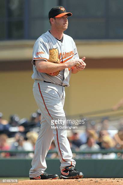 Kevin Millwood of the Baltimore Orioles rubs up a baseball during the first inning of a spring training game against the Detroit Tigers at Joker...