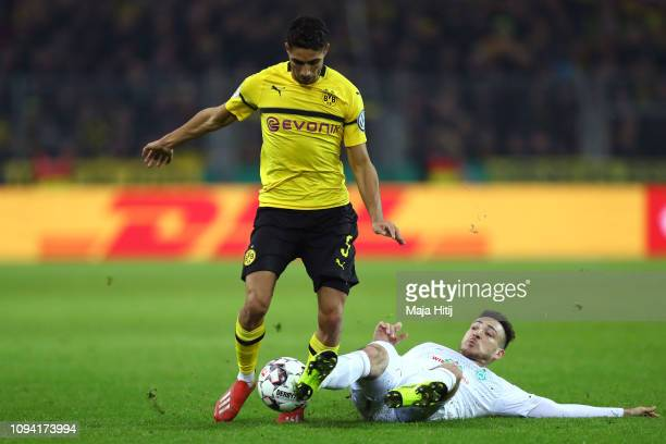 Kevin Mohwald of Werder Bremen tackles Achraf Hakimi of Borussia Dortmund during the DFB Cup match between Borussia Dortmund and Werder Bremen at...