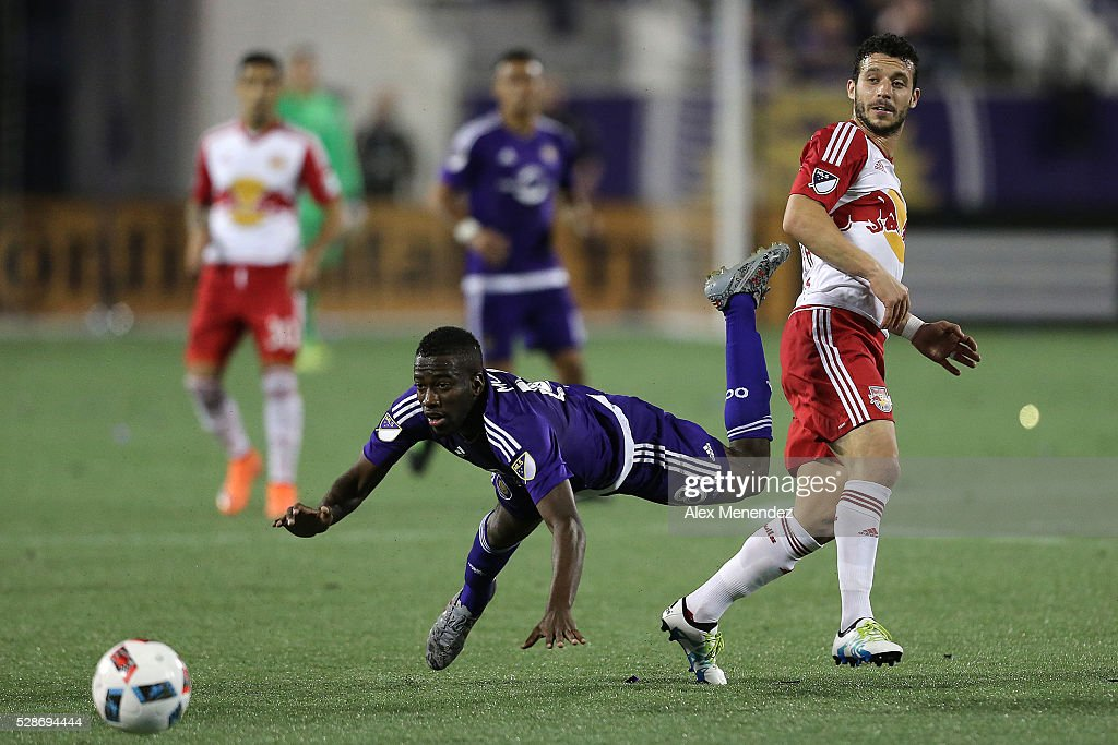 Kevin Molino #18 of Orlando City SC gets tripped up by Felipe Martins #8 of New York Red Bulls during an MLS soccer match at Camping World Stadium on May 6, 2016 in Orlando, Florida. The game ended in a 1-1 draw.