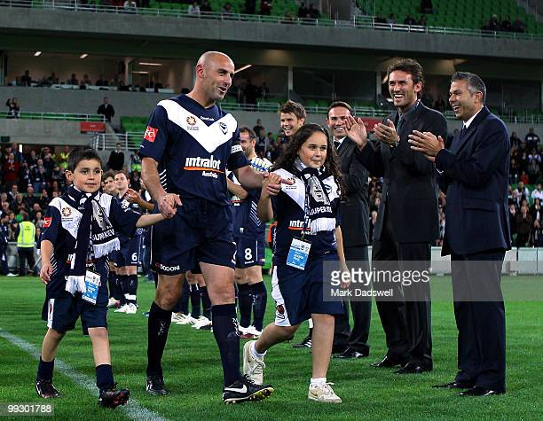 Kevin Muscat of the Victory with his children by his side walks through a guard of honour made up of teammates and former opponents during the Kevin...