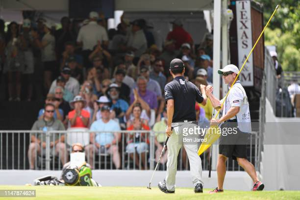 Kevin Na fist bumps with his caddie after making a putt on the eighth green during the final round of the Charles Schwab Challenge at Colonial...