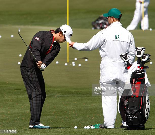 Kevin Na left has his caddie Kenneth Harms hold the bill of his cap to keep his head still on the practice range at the Augusta National Golf course...
