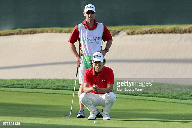 Kevin Na lines up a putt for a portion of the lead on the final hole as his caddie looks on in the background during the final round of the Valspar...
