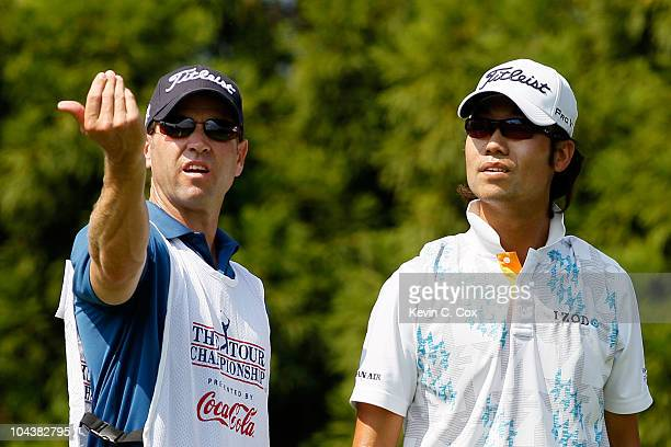 Kevin Na of South Korea talks with his caddie Kenny Harms before playing his tee shot on second hole during the first round of THE TOUR Championship...