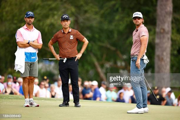 Kevin Na of the United States and Roger Sloan of Canada wait on the 18th green during the final round of the Wyndham Championship at Sedgefield...