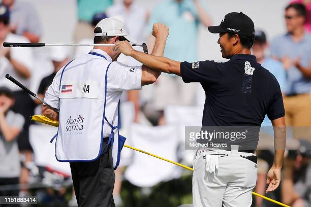 Kevin Na of the United States celebrates with caddie Kenny Harms on the 18th green after winning the Charles Schwab Challenge at Colonial Country...