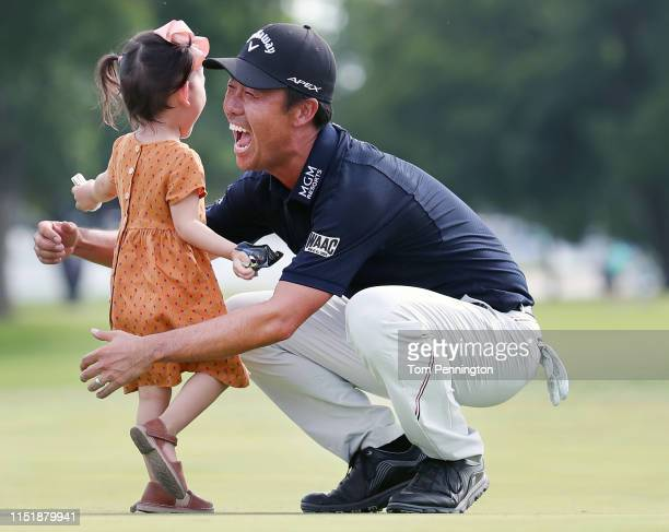 Kevin Na of the United States celebrates with his daughter Sophia Na on the 18th green after winning the Charles Schwab Challenge at Colonial Country...