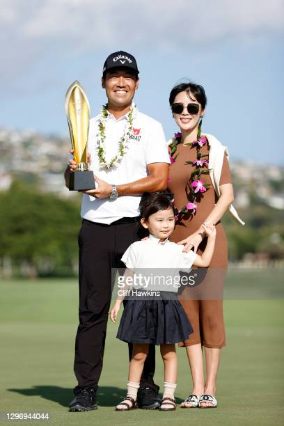 Kevin Na of the United States celebrates with the trophy alongside wife Julianne and daugther Sophia after winning the Sony Open in Hawaii at the...