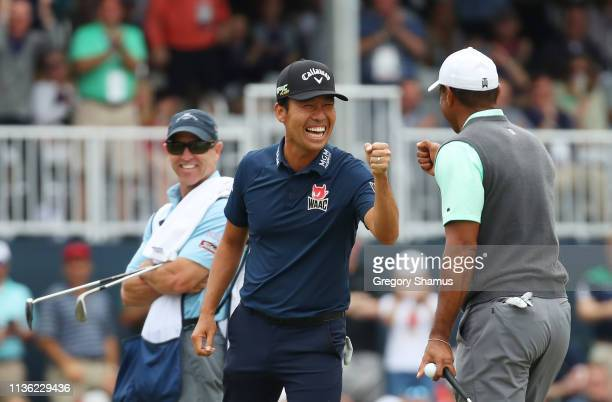 Kevin Na of the United States reacts with Tiger Woods of the United States on the 17th green during the third round of The PLAYERS Championship on...