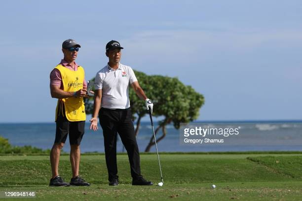 Kevin Na of the United States talks with caddie Kenny Harms on the 17th tee during the final round of the Sony Open in Hawaii at the Waialae Country...