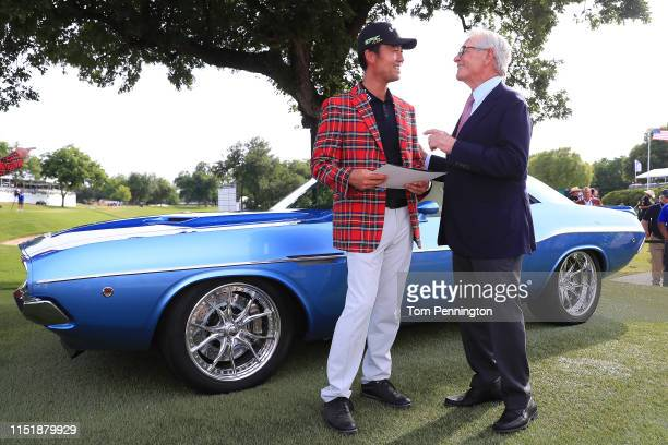 Kevin Na of the United States talks with Charles Schwab after he was presented with the keys to a fully restored 1973 Dodge Challenger for winning...