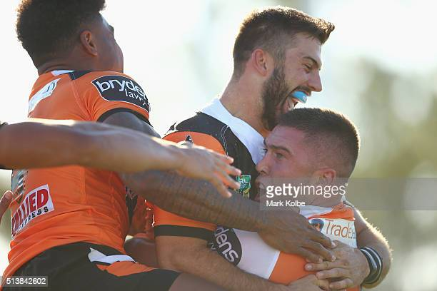 Kevin Naiqama and James Tedesco of the Tigers congratulate Curtis Sironen of the Tigers as he celebrates scoring a try during the round one NRL match...