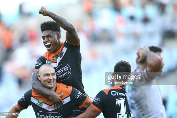 Kevin Naiqama of the Tigers celebrates on the shoulders of team mate Robert Rochow after winning the round one NRL match between the Wests Tigers and...
