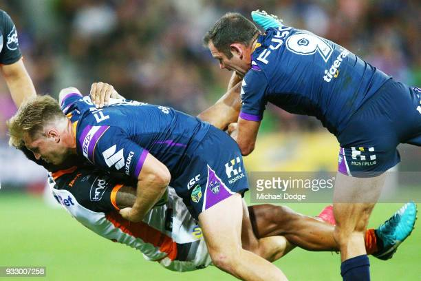 Kevin Naiqama of the Tigers was taken off after this tackle by Cameron Munster of the Storm and Cameron Smith during the round two NRL match between...