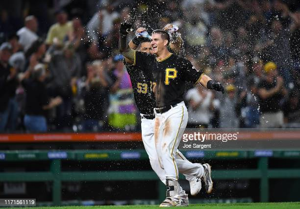 Kevin Newman of the Pittsburgh Pirates celebrates his two run home run with Melky Cabrera during the ninth inning against the Cincinnati Reds at PNC...