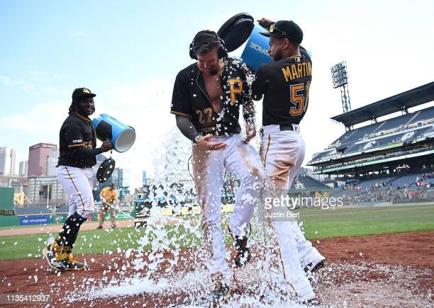 Kevin Newman of the Pittsburgh Pirates has water dumped on him by Jason Martin after hitting a walk off double in the 10th inning to give the Pirates...
