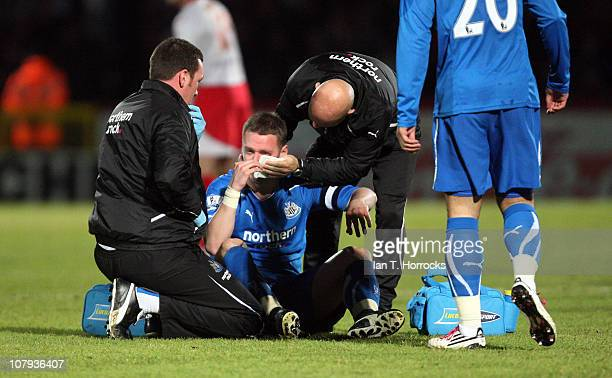 Kevin Nolan of Newcastle United receives treatment to his eye after getting hit in the face by the ball during the FA Cup sponsored by E.ON 3rd round...