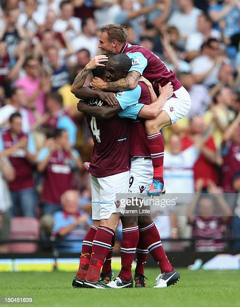 Kevin Nolan of West Ham United celebrates with team mates Carlton Cole and Matthew Taylor after scoring the opening goal during the Premier League...
