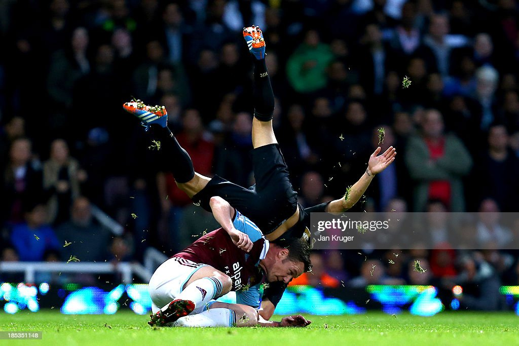 Kevin Nolan of West Ham United is booked for this tackle on David Silva of Manchester City during the Barclays Premier League match between West Ham United and Manchester City at the Boleyn Ground on October 19, 2013 in London, England.