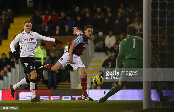 Kevin Nolan of West Ham United scores his side's first goal past Mark Schwarzer of Fulham during the Barclays Premier League match between Fulham and...