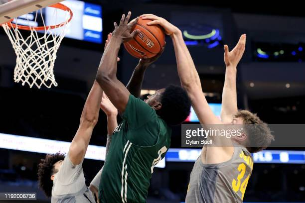 Kevin Norman of the Jacksonville Dolphins attempts a shot while being guarded by Brendan Bailey and Jayce Johnson of the Marquette Golden Eagles in...