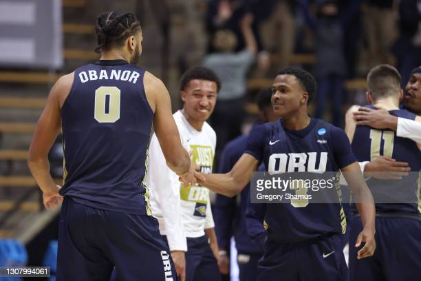 Kevin Obanor and Max Abmas of the Oral Roberts Golden Eagles react after defeating the Ohio State Buckeyes in overtime in the first round game of the...