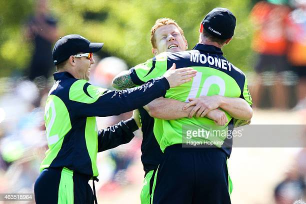 Kevin O'Brien of Ireland celebrates with teammates John Mooney and Niall O'Brien after taking the wicket of Dwayne Smith of the West Indies during...