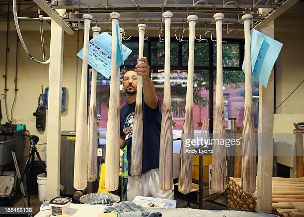 Kevin Olges hangs the World Series bats for both the St Louis Cardinals and the Boston Red Sox after working on the filler at the Louisville Slugger...