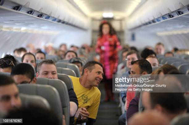 USA Kevin Osborne left Luis Fuentes chat as comedian Pam Ann strolls the aisle during JetBlue's JetPride flight 1969 from San Francisco to Long Beach...