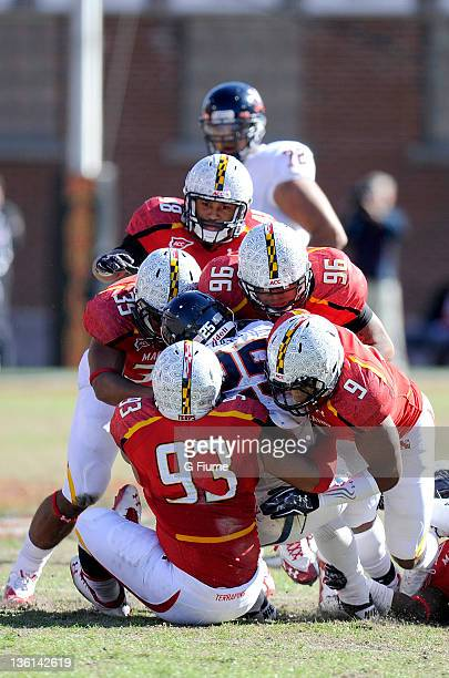 Kevin Parks of the Virginia Cavaliers is tackled by a pack of Maryland Terrapins at Byrd Stadium on November 5 2011 in College Park Maryland