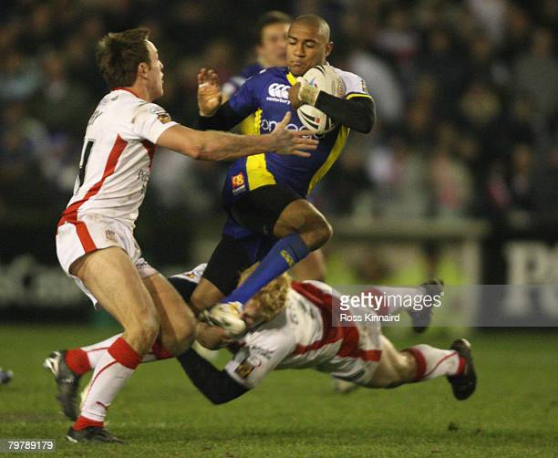 Kevin Penny of Warrington is tackled by James Roby and James Graham of St Helens during the Super Leaue match between St Helens and Warrington Wolves...