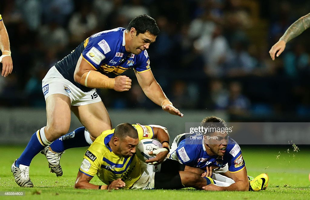 Kevin Penny of Warrington Wolves falls after a tackle by Joel Moon of the Leeds Rhinos during the Round 1 match of the First Utility Super League Super 8s between Leeds Rhinos and Warrington Wolves at Headingley Carnegie Stadium on August 7, 2015 in Leeds, England.