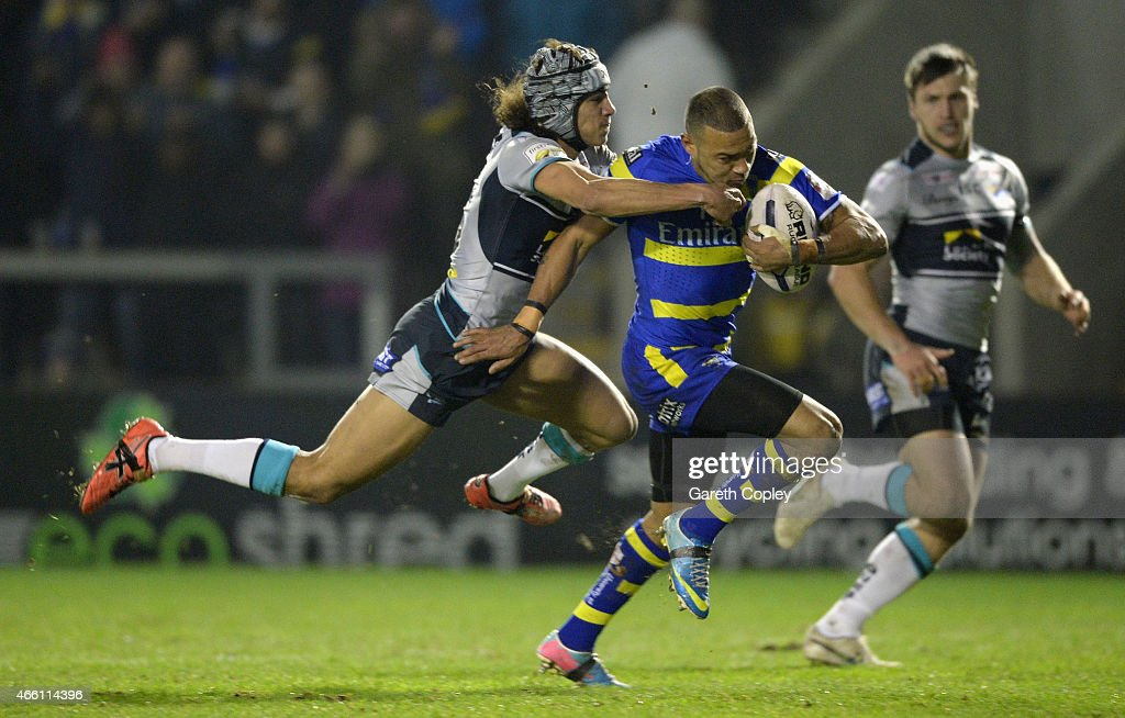 Kevin Penny of Warrington Wolves gets past Ashton Golding of Leeds Rhinos on his way to scoring the opening try during the First Utility Super League match between Warrington Wolves and Leeds Rhinos at The Halliwell Jones Stadium on March 13, 2015 in Warrington, England.