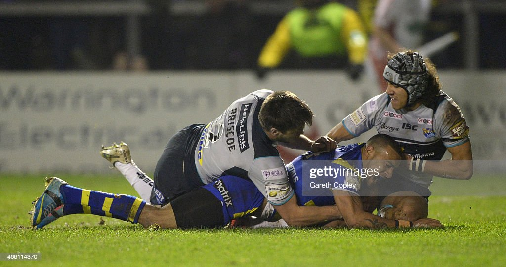Kevin Penny of Warrington Wolves scores his team's opening try past Tom Briscoe and Ashton Golding of Leeds Rhinos during the First Utility Super League match between Warrington Wolves and Leeds Rhinos at The Halliwell Jones Stadium on March 13, 2015 in Warrington, England.