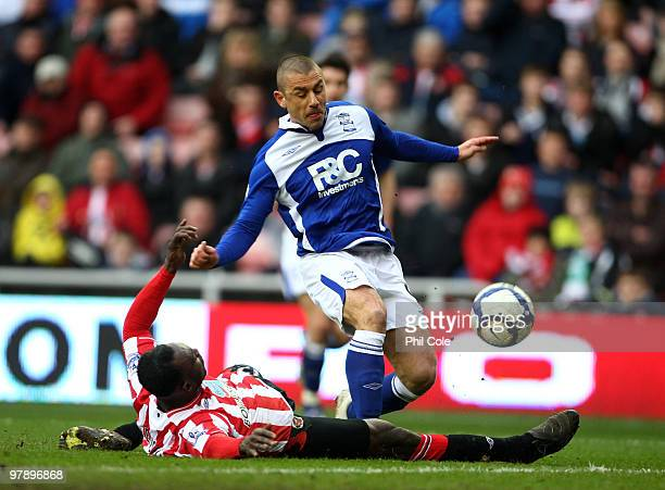 Kevin Phillips of Birmingham City is tackled by John Mensah of Sunderland during the Barclays Premier League match between Sunderland and Birmingham...