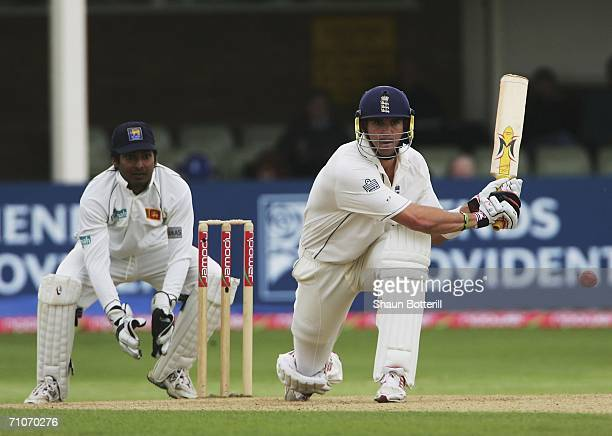 Kevin Pietersen of England plays a shot as Kumar Sangakkara the Sri Lankan wicketkeeper looks on during the 4th day of the 2nd Test Match between...