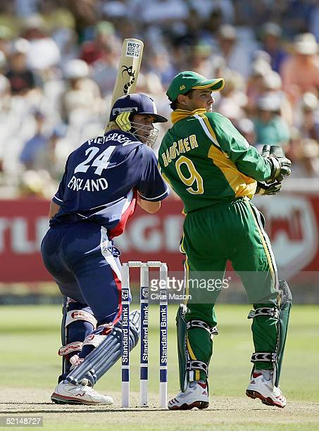 Kevin Pietersen of England plays a shot while on his way to a half century whilst Mark Boucher of South Africa looks on during the fourth one day...