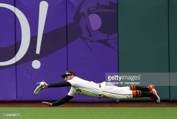 Kevin Pillar of the San Francisco Giants dives for the ball and watches it kick off his glove for a double off the bat of Rowdy Tellez of the Toronto...