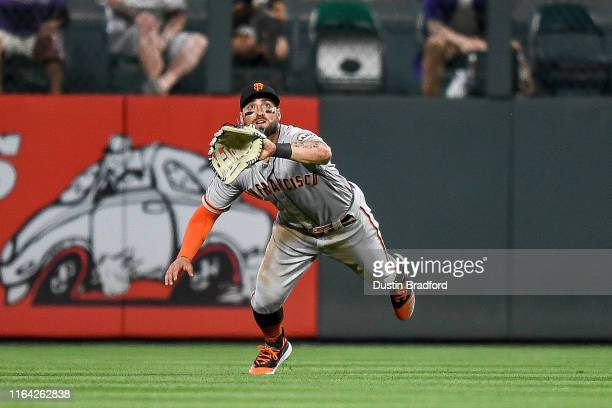 Kevin Pillar of the San Francisco Giants makes a diving catch in center field in the eighth inning of a game against the Colorado Rockies at Coors...