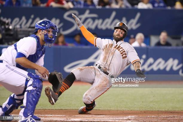 Kevin Pillar of the San Francisco Giants slides across home plate to score a run in the second inning during MLB game action against the Toronto Blue...
