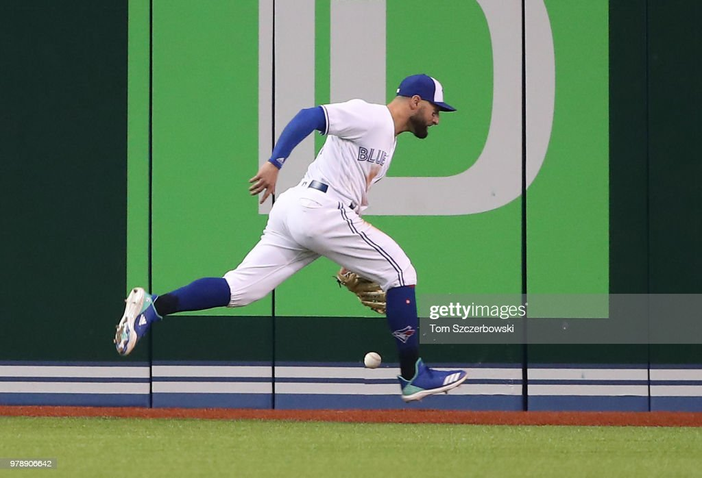 Kevin Pillar #11 of the Toronto Blue Jays cannot hold on to the ball in the sixth inning during MLB game action as Freddie Freeman #5 of the Atlanta Braves hits a triple at Rogers Centre on June 19, 2018 in Toronto, Canada.